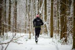Отображайте от задней части человека в sportswear, красной крышке на беге в зиме стоковое фото