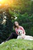 Отображайте снизу женщины сидя с собакой на зеленой лужайке Стоковое фото RF