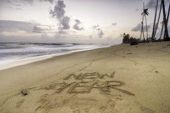 Отображайте с словом НОВЫМ ГОДОМ на песчаном пляже с красивым заходом солнца восхода солнца и развевайте подача ударяя берег Стоковое Изображение