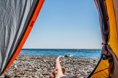 Отображайте человеческие ноги лежа в туристском шатре с взглядом моря Стоковое Изображение RF