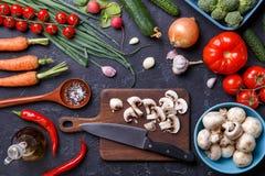 Отображайте na górze свежих овощей, грибов, разделочной доски, масла, ножа Стоковая Фотография RF