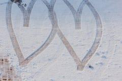 Отпечаток 2 сердец нарисованных в снеге Стоковые Изображения