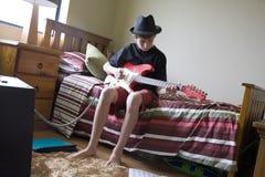 Отпочковываясь гитарист спальни стоковое фото