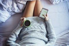Отправка СМС в кровати стоковое фото rf