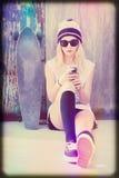 Отправка СМС девушки конькобежца Стоковое Фото