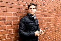 Отправка СМС к молодому человеку подруги красивому в умной вскользь носке держа мобильный телефон пока полагающся на кирпичной ст Стоковые Изображения