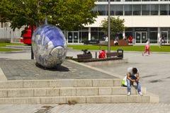 Отправка СМС молодого человека сидит около большой скульптуры рыб на набережной Donegall в районе гавани Белфаста, Северной Ирлан Стоковая Фотография RF