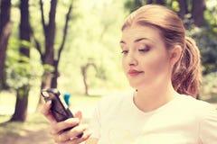 Отправка СМС расстроенной скептичной несчастной серьезной женщины говоря на телефоне Стоковое Изображение