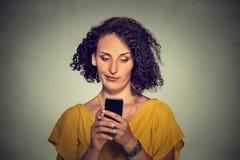 Отправка СМС расстроенной скептичной несчастной серьезной женщины говоря на телефоне Стоковые Фотографии RF