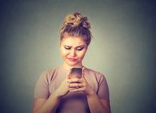 Отправка СМС расстроенной унылой скептичной несчастной женщины говоря на раздражанном телефоне Стоковое Изображение RF