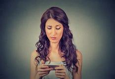 Отправка СМС расстроенной унылой скептичной несчастной серьезной женщины говоря на телефоне Стоковые Фото