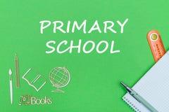 Отправьте СМС начальная школа, миниатюры школьных принадлежностей деревянные, тетрадь на зеленой предпосылке Стоковые Изображения