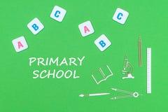 Отправьте СМС начальная школа, сверху деревянные школьные принадлежности minitures и письма abc на зеленой предпосылке Стоковые Фотографии RF