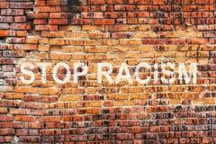 Отправьте СМС РАСИЗМ СТОПА на запятнанной старой оранжевой предпосылке текстуры кирпичной стены Стоковое Изображение RF