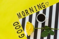 Отправьте SMS доброму утру, чашке кофе и желтой розе на стильной черно-белой салфетке на желтой предпосылке Минимальный стиль Кон стоковая фотография