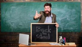 Отпразднуйте день знания Учитель или воспитатель приветствуют надпись назад к школе Воспитатель учителя опытный стоковое фото rf