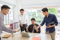 отпразднуйте успех Команда дела празднует хорошую работу в офисе азиатские люди Succes дела на мобильном телефоне и компьютере стоковые изображения rf