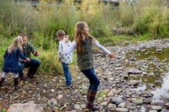 Отпрыски бросая утесы в реке совместно Стоковое Изображение RF