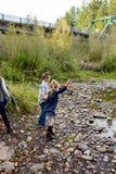 Отпрыски бросая утесы в реке совместно Стоковые Фотографии RF
