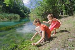 Отпрыски девушки и мальчика играя около воды реки Tirino итальянки Стоковые Изображения RF