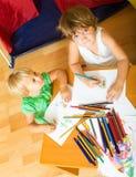 Отпрыски играя с карандашами Стоковое Изображение