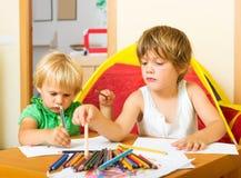 Отпрыски играя с карандашами Стоковые Изображения