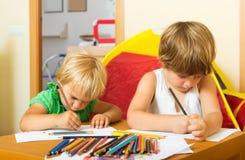 Отпрыски играя с карандашами Стоковое фото RF