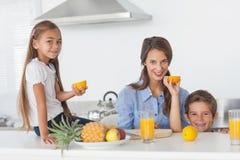 Отпрыски поднимая половинный апельсин в кухне Стоковое фото RF