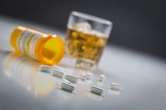 Отпускаемые по рецепту лекарства разлитые от упаденной бутылки около стекла Alco Стоковое Фото