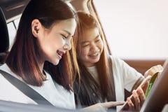 Отпуск и перемещение, перемещения красивых молодых женщин жизнерадостные совместно на расслабляющий праздник И хохот в автомобиле Стоковое Фото