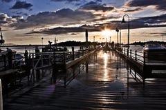 Отражать захода солнца светлый на влажной пристани рыбной ловли стоковое фото rf
