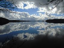 Отражать на отражении неба и гор на Loch Lomond стоковые изображения rf