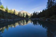 Отражение берега озера в водообильной поверхности Предыдущее солнечное утро Большое более низкое озеро Shavlinsky дни altai продо стоковая фотография rf