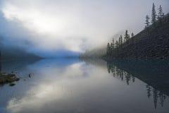 Отражение берега озера в водообильной поверхности Туманное утро лета Большое более низкое озеро Shavlinsky также стоковые изображения