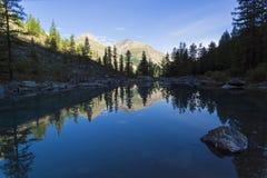 Отражение берега озера в водообильной поверхности стоковые фотографии rf