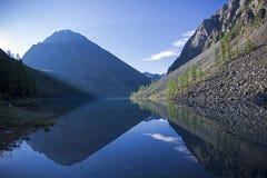 Отражение берега озера в водообильной поверхности стоковое фото