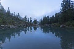 Отражение берега озера в водообильной поверхности стоковое фото rf