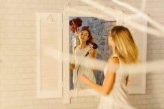 Отражение белокурого подростка суша ее волосы стоковые фотографии rf