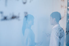 Отражение бизнесмена и коммерсантки говоря в офисе Стоковая Фотография RF