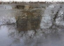 Отражение большого дома в коричневой лужице на влажном асфальте, чуть-чуть деревьев рядом с домом и края белого снега Стоковое Фото