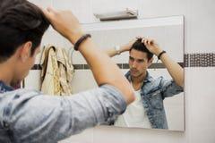 Отражение волос втулки человека в зеркале Стоковые Изображения