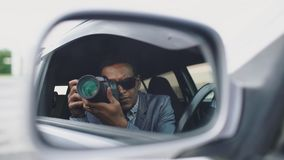 Отражение в бортовом зеркале папарацци укомплектовывает личным составом сидеть внутри автомобиля и фотографировать с камерой dslr Стоковые Изображения