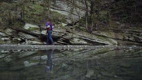 Отражение в воде девушки которая идет вдоль каменной скалы сток-видео
