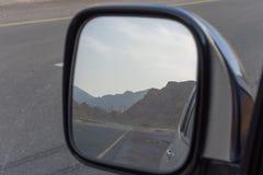 Отражение в зеркале стороны вида сзади дороги пока управляющ вдоль дороги горы Jebal Jais в Рас-Аль-Хайма, Объениненных Арабских  стоковое изображение