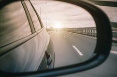 Отражение в зеркале заднего вида автомобиля и дорога освещают Стоковая Фотография RF