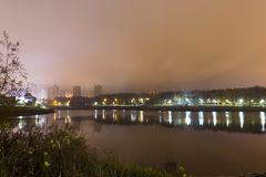 Отражение города со светами ночи в озере стоковые фотографии rf