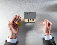 Отражение для дома арендовать, продавать или покупать в руках бизнесмена Стоковое Изображение RF