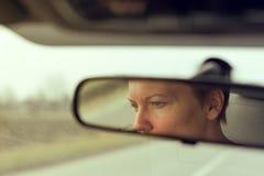 Отражение женской стороны в зеркале заднего вида автомобиля Стоковое Фото