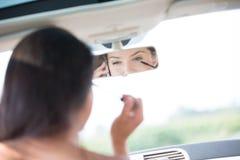 Отражение женщины используя сотовый телефон пока прикладывающ тушь в зеркале заднего вида автомобиля Стоковая Фотография
