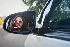 Отражение жизнерадостной красивой девушки в бортовом зеркале автомобиля Стоковое фото RF